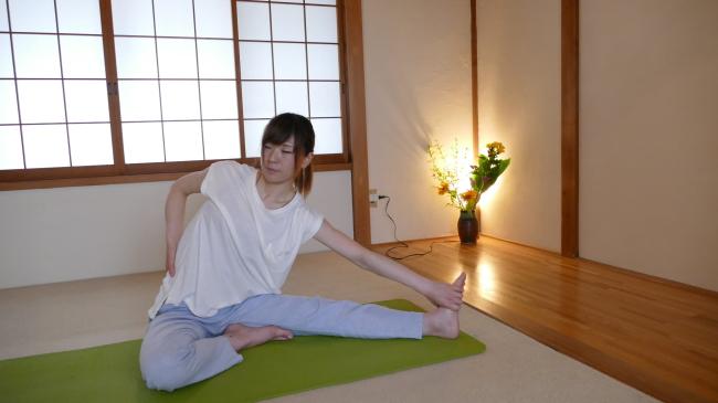 上記のストレッチの姿勢から片手を放し腰の横に当てます。片方の手は足をつかみます。
